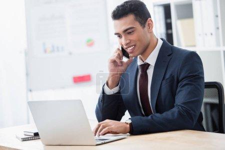Foto de Sonriente a joven empresario hablando por teléfono inteligente y trabajar con el portátil en la oficina - Imagen libre de derechos