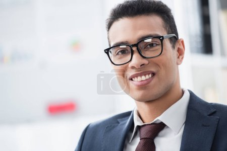 portrait of handsome young businessman in eyeglasses smiling at camera