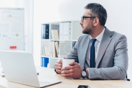 thoughtful businessman in eyeglasses holding cup of coffee and looking away while sitting at workplace