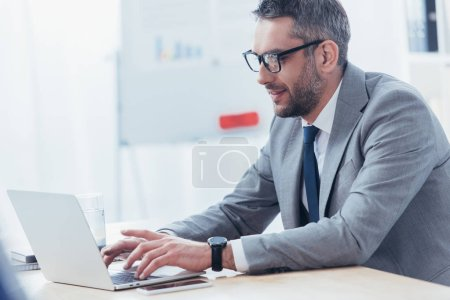 smiling bearded businessman in eyeglasses using laptop at workplace