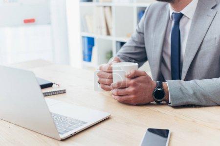 Foto de Tiro corto del empresario sosteniendo la taza de café y sentado en la mesa con ordenador portátil - Imagen libre de derechos