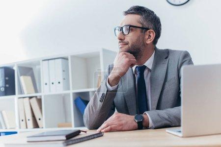 cher homme d'affaires à lunettes assis sur le lieu de travail et regardant loin
