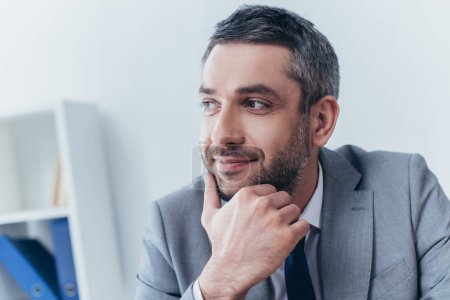portrait of handsome smiling bearded businessman with hand on chin looking away in office