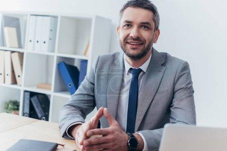 hombre de negocios guapo sentado en el lugar de trabajo y sonriendo a la cámara