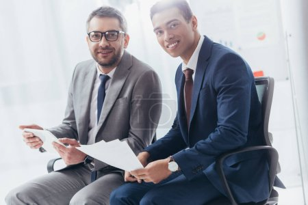 two professional businessmen smiling at camera while working with papers and digital tablet in office
