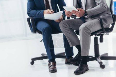 Photo pour Plan recadré d'hommes d'affaires en tenue formelle travaillant avec des papiers et tablette numérique au bureau - image libre de droit