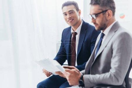 Foto de Joven empresario sosteniendo papeles y sonriendo a la cámara mientras que colega masculino en gafas con tableta digital en la oficina - Imagen libre de derechos