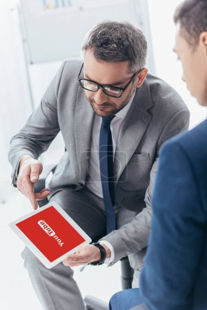 Foto de Recortar la captura de empresario en gafas mostrando tableta digital con aplicación de youtube para hombre colega en la oficina - Imagen libre de derechos