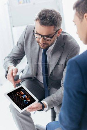 Photo pour Recadrée tir d'homme d'affaires en lunettes de vue montrant une tablette numérique avec les tableaux de l'entreprise à un collègue masculin au bureau - image libre de droit