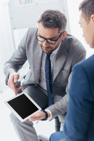 Photo pour Recadrée tir d'homme d'affaires en lunettes de vue montrant une tablette numérique avec écran blanc à un collègue masculin au bureau - image libre de droit