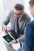 """Постер, картина, фотообои """"обрезанное выстрел бизнесмена в очки, показывая цифровой планшет с бизнес графиков на экране мужской коллеге в офисе"""""""