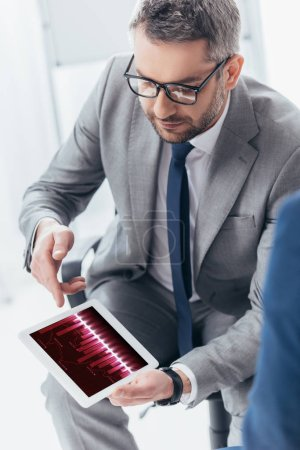 Photo pour Vue grand angle beau homme d'affaires de lunettes à l'aide de tablette numérique avec les cartes d'affaires - image libre de droit