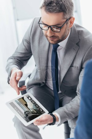 high angle view of handsome businessman in eyeglasses using digital tablet with tickets app on screen