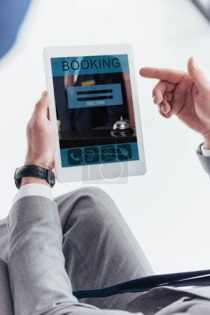 Photo for Partial view of businessman using digital tablet with booking application on screen - Royalty Free Image