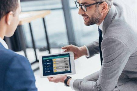 Photo pour Plan recadré de l'homme d'affaires dans les lunettes montrant tablette numérique avec l'application paris sportifs à l'écran pour collègue masculin au bureau - image libre de droit