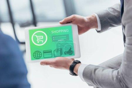 Foto de Vista parcial del empresario con tableta digital con aplicación de compras - Imagen libre de derechos