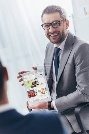 Photo for Smiling businessman in eyeglasses holding digital tablet with ebay application on screen - Royalty Free Image