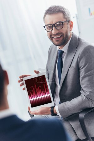 smiling businessman in eyeglasses holding digital tablet with business charts on screen
