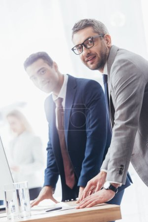 Photo for Professional businessmen leaning at table and smiling at camera in office - Royalty Free Image