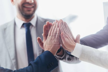 cropped shot of professional  business team giving high five in office