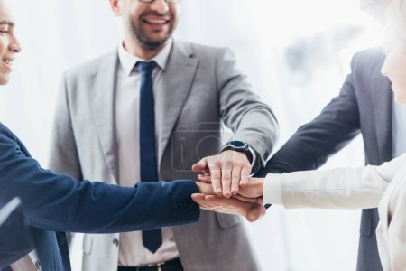 Photo for Cropped shot of happy business team stacking hands in office - Royalty Free Image