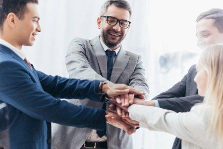 Photo pour Heureuse équipe d'affaires empilant les mains dans le bureau - image libre de droit