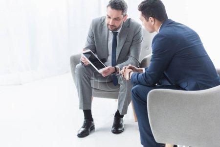 Photo pour Homme d'affaires sérieux montrant tablette numérique avec écran blanc pour jeune collègue au bureau - image libre de droit