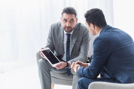 mentor d'affaires sérieuses tenant une tablette numérique avec écran blanc et regardant jeune collègue au bureau