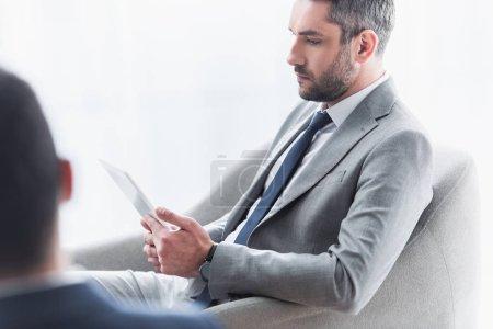 hombre de negocios barbudo serio sentado y usando tableta digital en la oficina