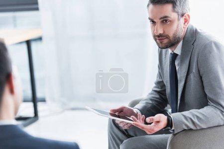 Foto de Recortada la foto del empresario con tableta digital y mirando hombre colega en la oficina - Imagen libre de derechos