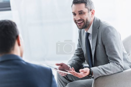 Photo for Smiling young businessman holding digital tablet and looking at male colleague on foreground - Royalty Free Image