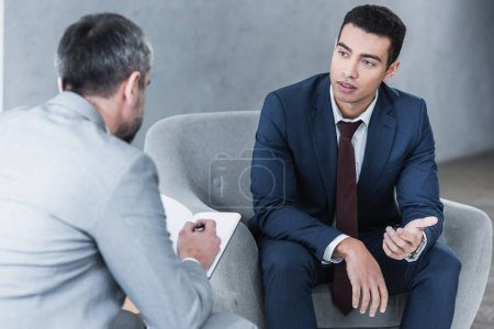 young businessman talking and looking at male colleague sitting and taking notes in notebook