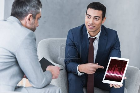 Photo pour Souriant le jeune homme d'affaires, pointant à la tablette numérique avec des graphiques sur l'écran et en regardant collègue masculin au cours de la conversation - image libre de droit