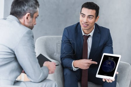 Photo pour Homme d'affaires jeune souriant pointant sur tablette numérique et en regardant collègue masculin au cours de la conversation - image libre de droit