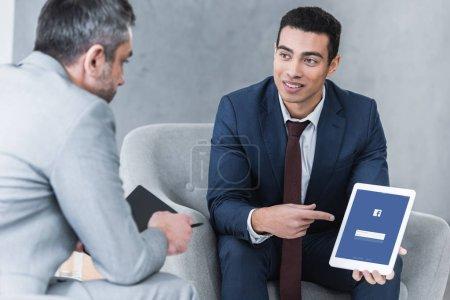 Foto de Sonriente a joven empresario señalando la tableta digital con aplicación de facebook en la pantalla y mirar colega masculino durante la conversación - Imagen libre de derechos
