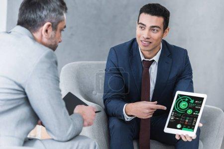 Photo pour Souriant le jeune homme d'affaires, pointant à la tablette numérique avec cartes d'affaires sur l'écran et en regardant collègue masculin au cours de la conversation - image libre de droit