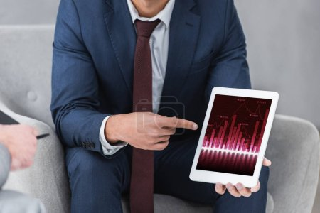 cropped shot of businessman in formal wear pointing with finger at digital tablet with business charts