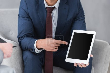 Photo for Cropped shot of businessman in formal wear pointing with finger at digital tablet with blank screen - Royalty Free Image