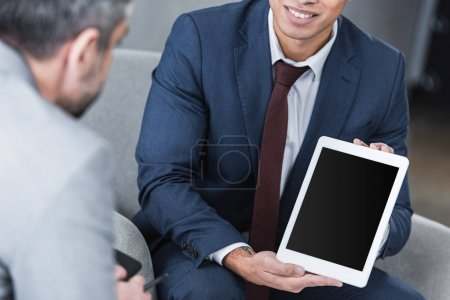 cropped shot of smiling young businessman showing digital tablet with blank screen to colleague
