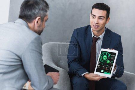 Photo pour Jeune homme d'affaires souriant montrant tablette numérique avec des graphiques d'affaires à son collègue - image libre de droit