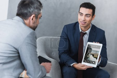 smiling young businessman showing digital tablet with tickets app to colleague