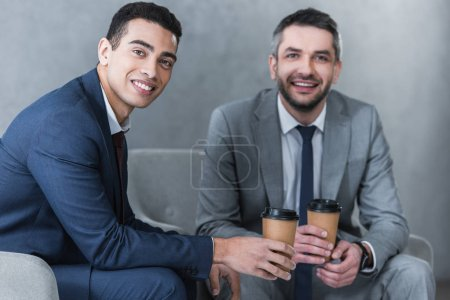 Photo for Professional businessmen holding coffee to go and smiling at camera while sitting together - Royalty Free Image