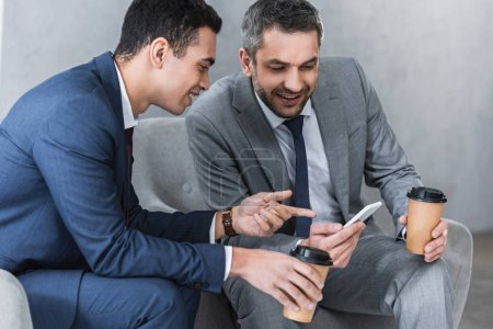 Photo for Smiling businessmen holding coffee to go and using smartphone together - Royalty Free Image
