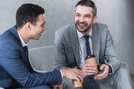 Photo pour Hommes d'affaires gais boire du café dans des tasses en papier et parler ensemble - image libre de droit