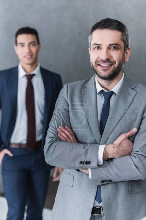 Photo for Confident businessman standing with crossed arms and smiling at camera while young colleague standing behind - Royalty Free Image