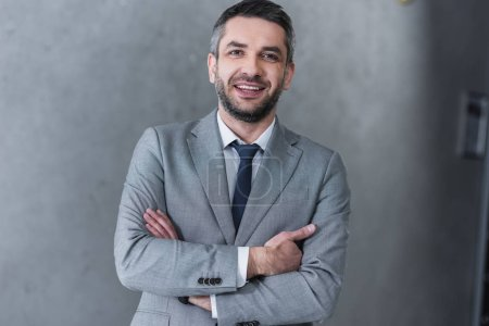 Photo pour Bel homme d'affaires confiant debout avec les bras croisés et souriant à la caméra - image libre de droit
