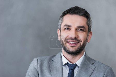 Photo pour Portrait d'un bel homme d'affaires confiant en tenue formelle souriant à la caméra sur fond gris - image libre de droit