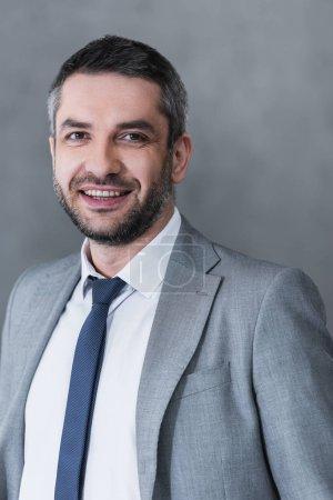 Foto de Apuesto hombre de negocios feliz en desgaste formal sonriendo a cámara en gris - Imagen libre de derechos
