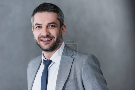 Photo for Portrait of handsome businessman in formal wear smiling at camera on grey - Royalty Free Image