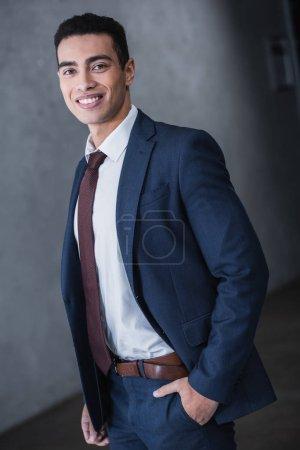 Foto de Retrato de hombre de negocios guapo joven raza mixta de pie con la mano en el bolsillo y sonriendo a cámara - Imagen libre de derechos